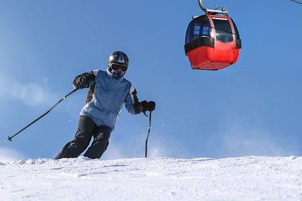 Skiier with Gondola Overhead