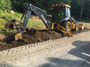 A yellow utility vehicle digging up an unpaved road during construction
