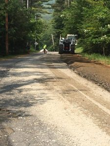 An unpaved dirt road partially worked on by a construction vehicle.