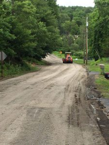 An orange tractor driving down an unpaved dirt road in the countryside
